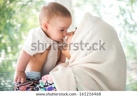 Women with an islamic scarf holding a gorgeous toddler - stock photo