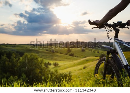 Women with bicycle riding country road  - stock photo