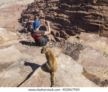 Women (with cat on the foreground) takes photo from the cliff edge of High Place of Sacrifice. Petra. Jordan.  - stock photo