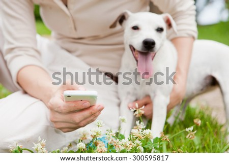 women with dog using smartphone on clover lawn