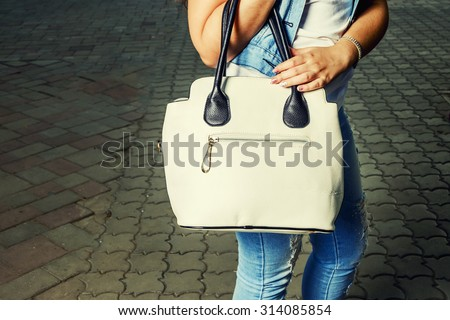 Women with fashionable handbag. Beautiful fashion woman wear vintage tight jeans, white hand bag and denim jacket. Toned in warm colors. Outdoors shot, lifestyle.  - stock photo