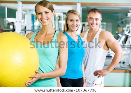 Women with  fitness trainer in the gym - stock photo