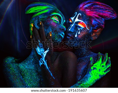 Women with fluorescent body art. Black background.