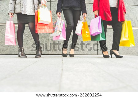 Women with high heels and shopping bags - Three girls standing and chatting after buying presents - stock photo