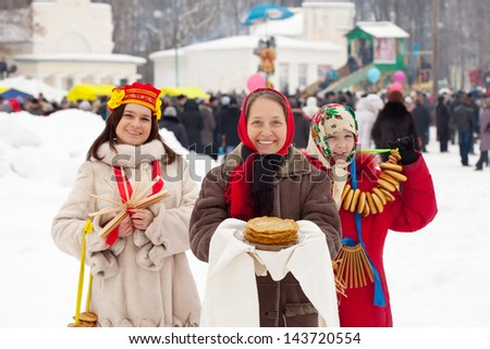 women  with pancakes and round cracknel during  Shrovetide in Russia