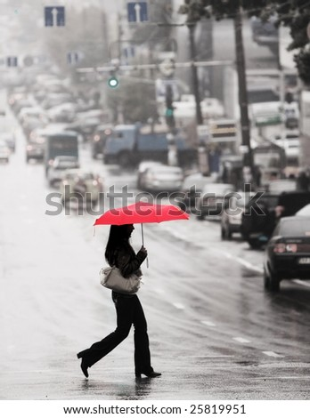 women with red umbrella cross the street in the rain - stock photo