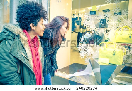 Women with shopping bags - Portrait of two pretty girls walking and looking at shops - Tourists buying clothes and presents - stock photo