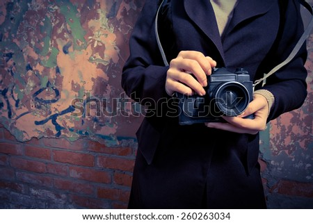 Women with vintage unrecognisable photocamera in her hands and a lot of copyspace - stock photo