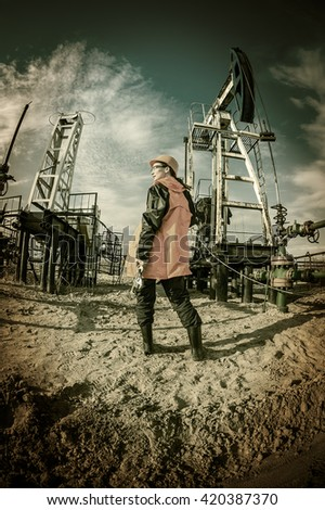 Women worker in the oil field, with wrenches in a hands, orange helmet and work clothes. Industrial site background. Toned. - stock photo