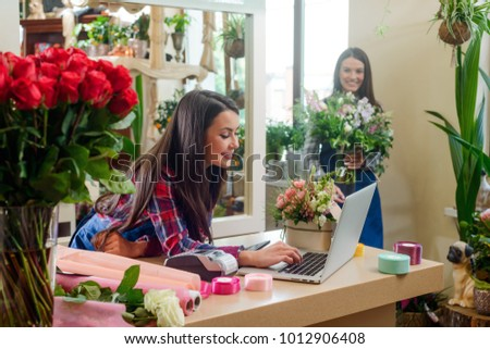 Women working in flower shop. Sales manager consults a buyer, while florist creates a bouquet. Friendly atmosphere between co-workers.