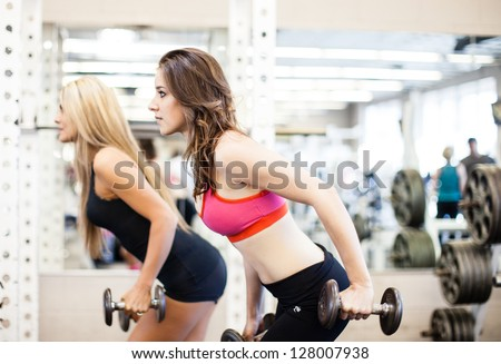 Women working on their triceps with dumbbells at the gym - stock photo