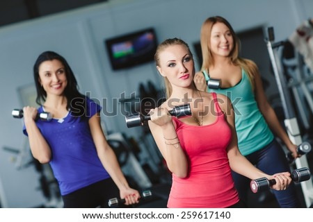 Women working on their triceps with dumbbells at the gym. Image of smiling woman and guy doing lifting exercise with barbells in hands - stock photo