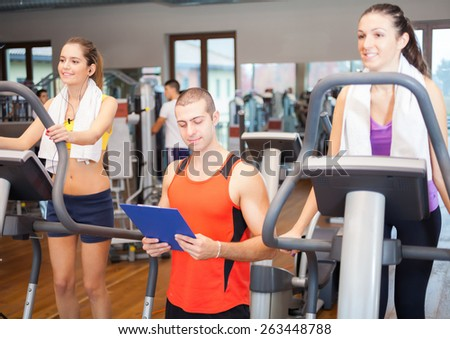 Women working out in a gym under the guide of a personal trainer - stock photo