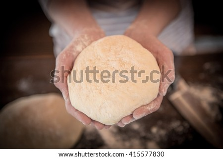 Womens hands holding a finished clean dough