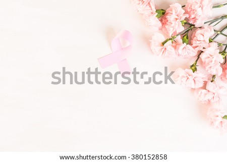 Womens health symbol in pink ribbon on wooden board. - stock photo