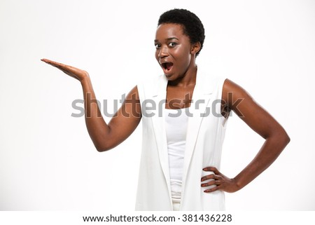 Wondered excited african american young woman standing and holding copyspce on palm over white background - stock photo