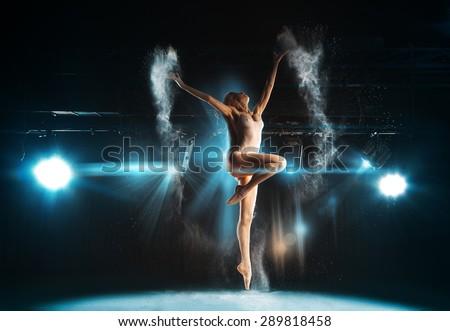 Wonderful adult ballerina posing on stage against spotlights in theater - stock photo