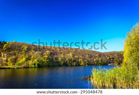 Wonderful  autumn wood and blue  river. - stock photo