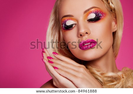 wonderful blond woman with creative make up on pink background