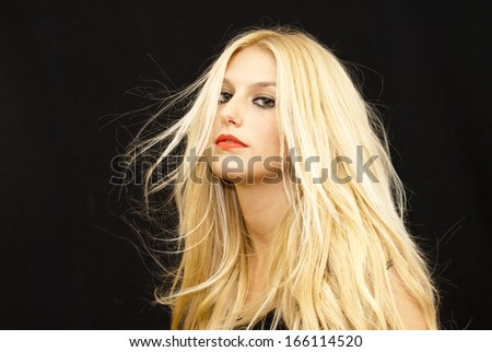 Wonderful blonde woman with hair in the wind on black background