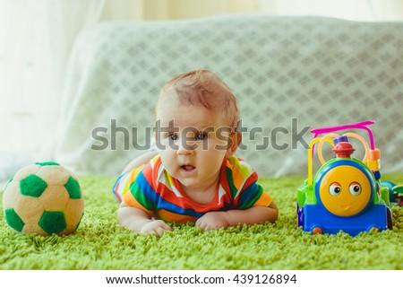 wonderful cheerful boy lying on the bed - stock photo