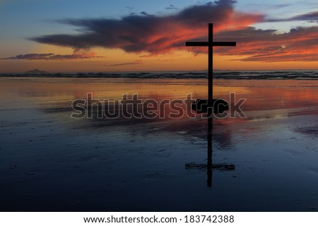 Wonderful colors of sunset behind a black cross. - stock photo