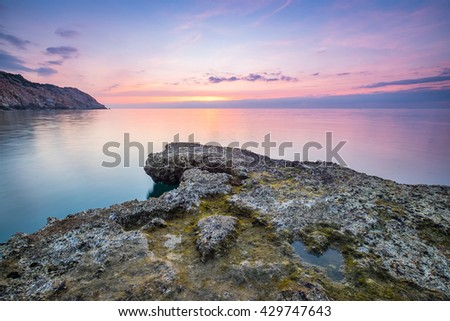 Wonderful dawn over large rock in calm waves at Nui Chua national park, Ninh Thuan Province, Viet Nam, one of amazing landscape in Vietnam, masterpiece place for travel.