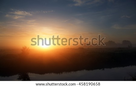 wonderful dramatic scene. fantastic foggy sunrise over the meadow with colorful clouds on the sky. picturesque rural landscape, misty morning. color in nature. beauty in the world - stock photo