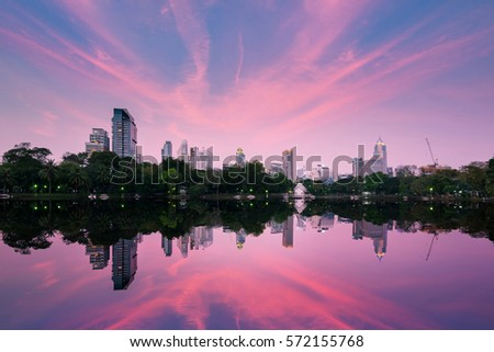 Wonderful evening period cityscape at Lumphini Park, Bangkok, Thailand. Night scene skyline at dusk with business district cityscape and water reflection from a park with twilight time.