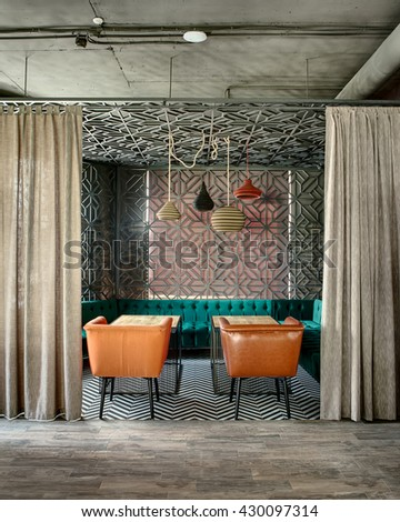 Wonderful interior in a loft style in a mexican restaurant. There is a zone decorated with metal lattices and curtains. In the zone there are green sofas, brown chairs, wooden tables and multi-colored - stock photo