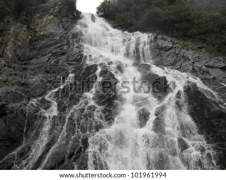 Wonderful landscape Small mountain waterfall rushing over the rocks - stock photo