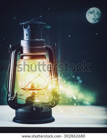 Wonderful night and vintage magic lantern on the window, abstract holidays background - stock photo