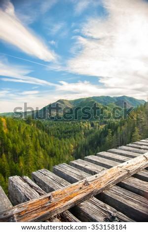Wonderful panorama of green mountains and sky in visible from the wood railway bridge - stock photo