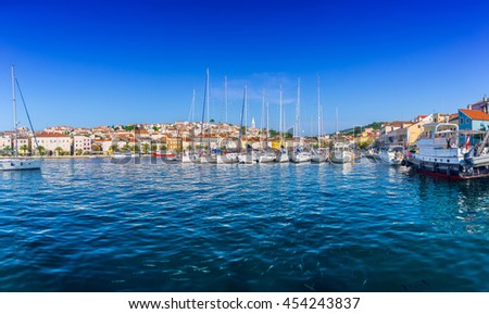 Wonderful romantic old town at Adriatic sea. Boats and yachts in harbor at magical summer. Fishes in the water surface on the foreground. Mali Losinj on the island of Losinj. Croatia. Europe.