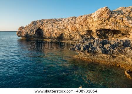 Wonderful sea landscape. Rocky shore calm sunny morning. Quiet clear sea. - stock photo