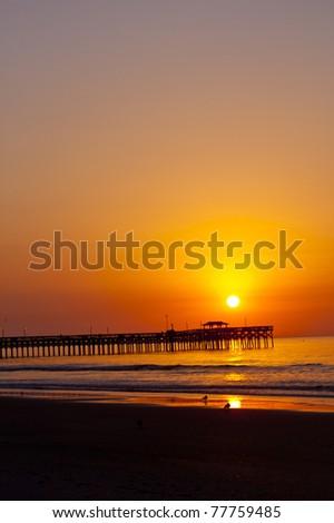 wonderful shot of the sun rising over a pier at an ocean beach - stock photo