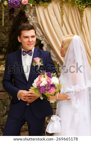 wonderful stylish rich happy bride and groom holding hands at a wedding ceremony in  garden near arch with flowers