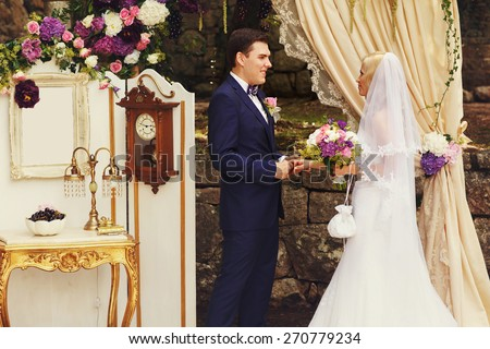 wonderful stylish rich happy bride and groom holding hands look et each other at a wedding ceremony in  garden near arch with flowers