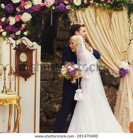wonderful stylish rich happy bride and groom huging look et each other at a wedding ceremony in  garden near arch with flowers - stock photo