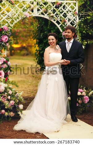 wonderful stylish rich happy bride and groom smiling at a wedding ceremony holding hands look at each other in green garden near white arch with flowers Rome Italy  - stock photo