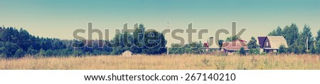 Wonderful summer panoramic view of the village and meadow. Toning effect done with a vintage retro Instagram style filter - stock photo