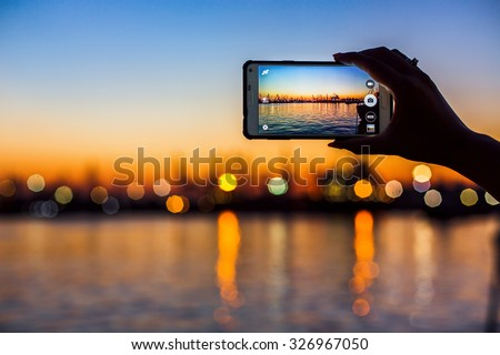 Wonderful sunset over sea harbor, tourist taking a picture of the seaport - stock photo