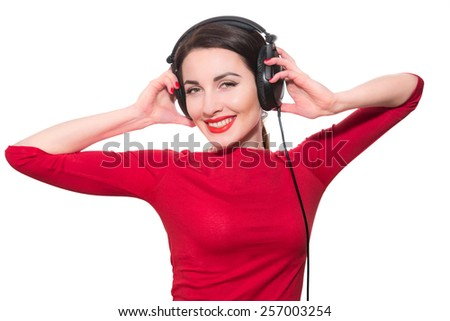 Wonderful teenager girl  listening to the music in big headphones in red clothes islolated on white background - stock photo