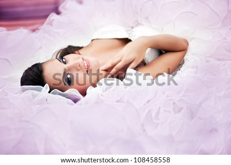 wonderful tender bride lies in a wedding dress - stock photo