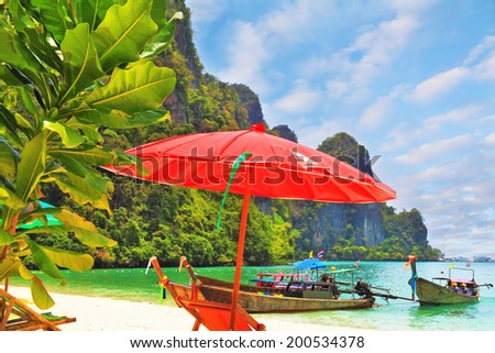 Wonderful vacation in the southern seas. Bright red parasol and sunbed near the sea. At the water's edge approached by native boats for tourists