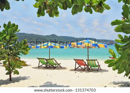 Wonderful vacation in the southern seas. Colorful beach umbrellas and sun beds for a rest on a sandy beach near the sea