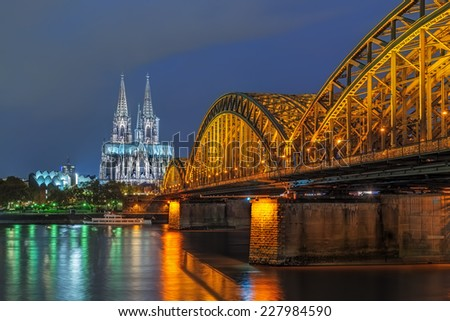 Wonderful view of Cologne cathedral and the Hohenzollern bridge illuminated at night in high dynamic range - stock photo