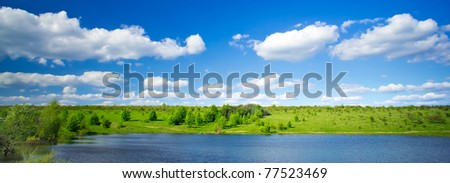 Wonderful view of lake and  green meadow by springtime.