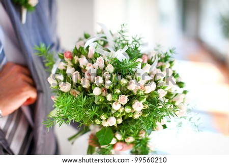 Wonderful wedding bouquet of beautiful roses, which a groom is holding in a hand before bridal ceremony. - stock photo