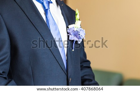 Wonderful wedding boutonniere on a costume of groom close-up - stock photo